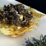Niuet de butifarra. Nido de patatas finas fritas con un salteado de botifarra con cebolla caramelizada.